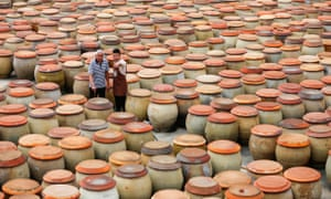 Wu Huaqing and his grandfather Wu Zongzhong patrol among soy sauce jars at his company in Quanzhou, southeast China's Fujian Province. Soy sauce is among the products that will be faced with the 25% tariff