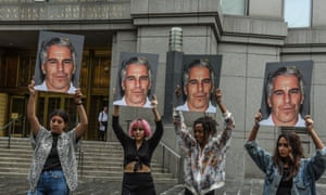 A protest group holds up photos of Jeffrey Epstein in front of the courthouse in New York City on 8 July 2019.