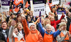 People hold placards during a rally for equal pay for Glasgow council workers.