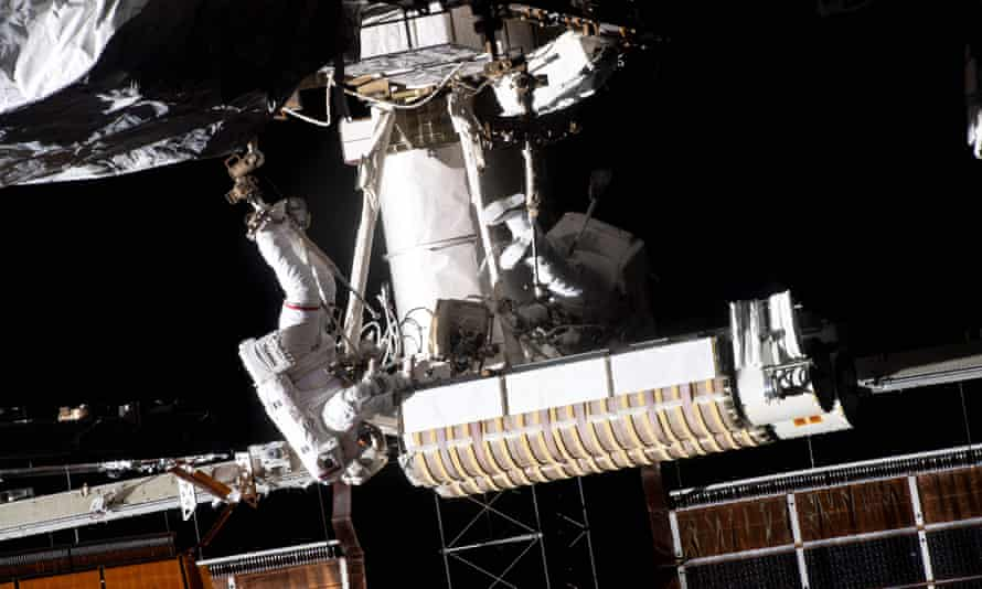 Thomas Pesquet (left) of the European Space Agency is attached to a portable hinged footrest at the end of the Canadarm2 robotic arm carrying new solar panels to the P-6 truss structure of the International Space Station, next to it by American astronaut Shane Kimbrough.