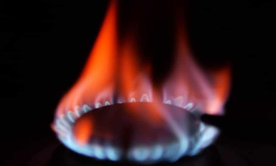 A gas ring burns blue and red flames