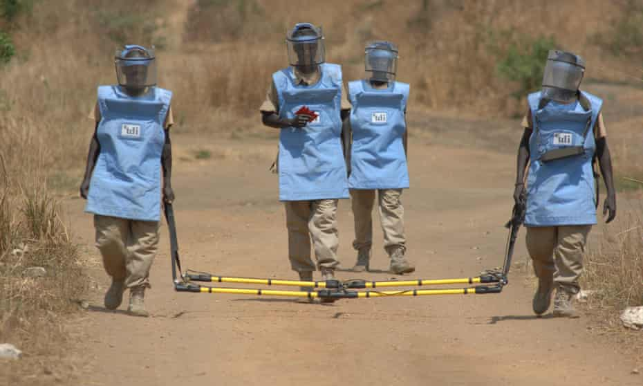 A specialist group of deminers use a piece of scanning equipment known as a broadloop to scan and mark a road in South Sudan suspected of being mined.