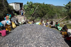 Children and adults fill bags with mica to be transported by a truck.