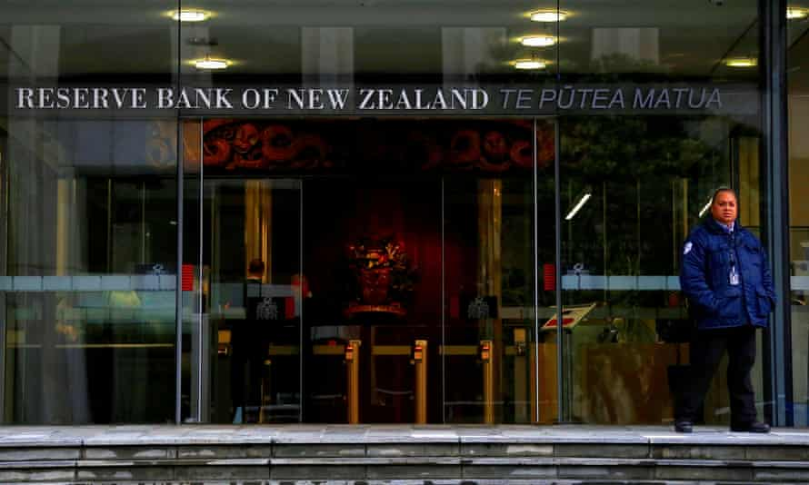 A security guard stands outside the main entrance to the Reserve Bank of New Zealand in central Wellington