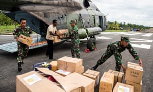 Indonesian soldiers along with a local resident unload food and medical aid in Asmat, a remote region of Papua, last week.