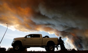 People wait at a roadblock as smoke rises from wildfires near Fort McMurray, Alberta.