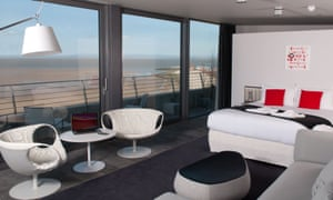 Seating and a bed in a room with walled windows overlooking the sea