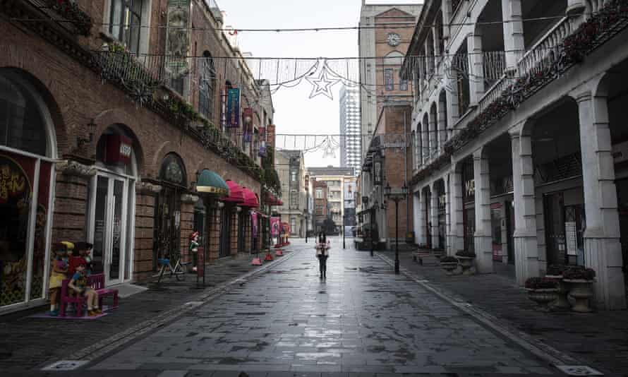 A woman walks down an otherwise deserted street in Wuhan.