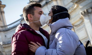 A couple kiss wearing face masks in Rome.