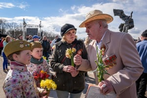 A man speaks to children as Latvia's large Russian minority holds festivities at Riga's Victory Monument.