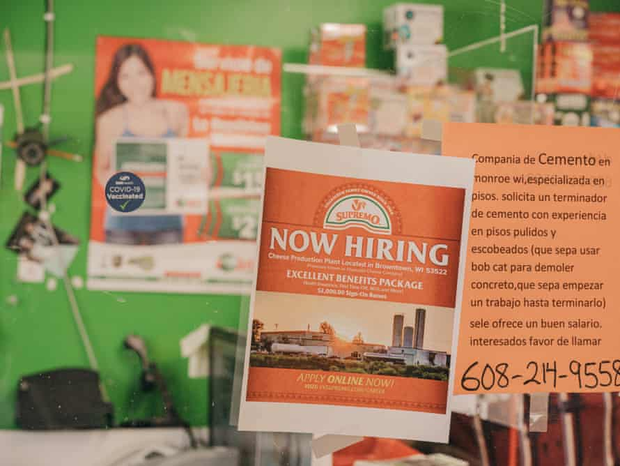 Orange signs advertising job openings in English and Spanish hang on a clear partition at the Veracruz Mexican market.