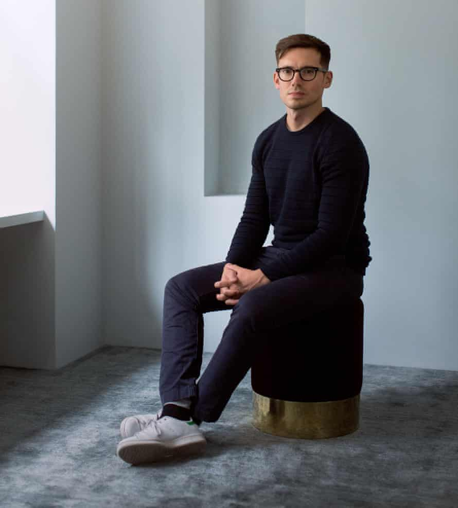 Erdem Moralioğlu sitting on a stool, feet and hands crossed, looking at the camera