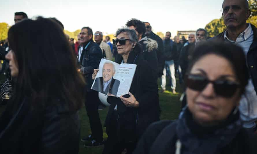 People watch the national homage to Aznavour broadcast on a giant screen at the Esplanades des Invalides in Paris.