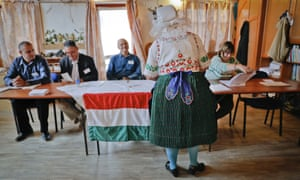 Edit Piros, an ethnic Hungarian from Romania, who moved to Hungary from Transylvania, receives the ballot paper before voting in the referendum in the village of Veresegyhaz, Hungary.