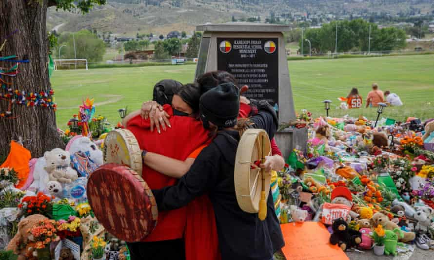 Members of the Mosakahiken Cree Nation hug in front of a makeshift memorial at the former Kamloops Indian Residential School to honor the 215 children whose remains have been discovered buried near the facility, in British Columbia.