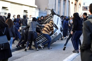 Protesters overturn a car in the street