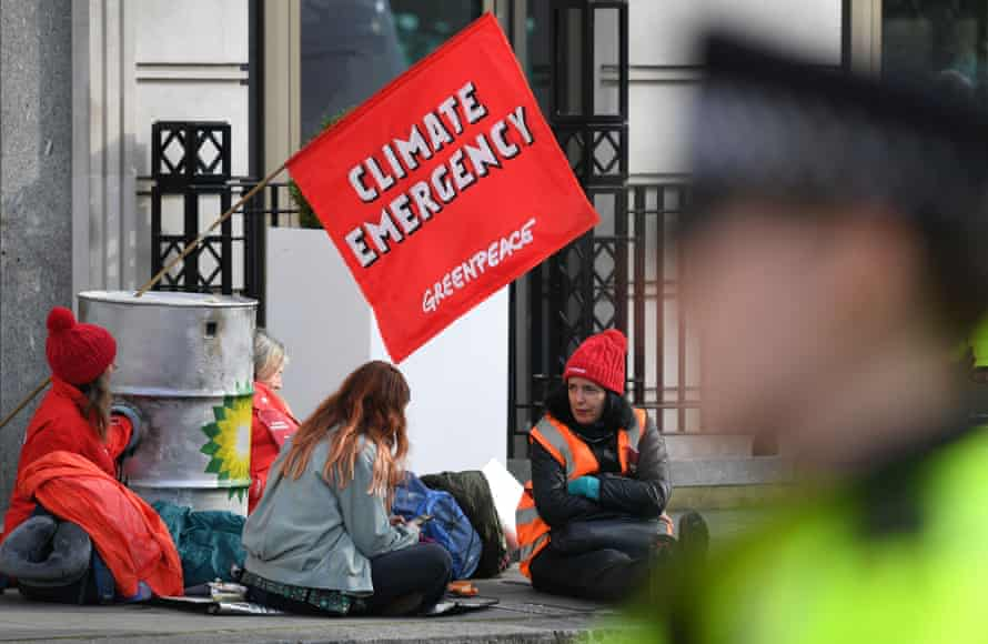 Greenpeace activists chain themselves to oil barrels outside BP's headquarters in London.