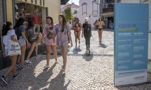 Young women walk by a Covid-19 warning poster last week on their way to Praia da Rainha in Cascais, Portugal