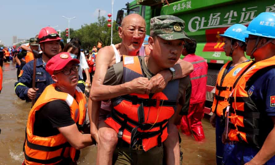 Rescuers move people out of a flooded zone as part of an evacuation effort in Weihui city in central China's Henan province on 26 July.
