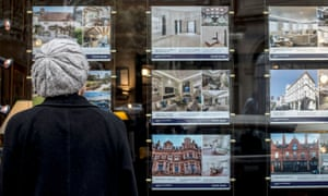 A woman looking at houses for sale in the window of an estate agents in London.