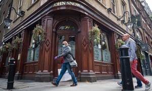People walk past closed pub