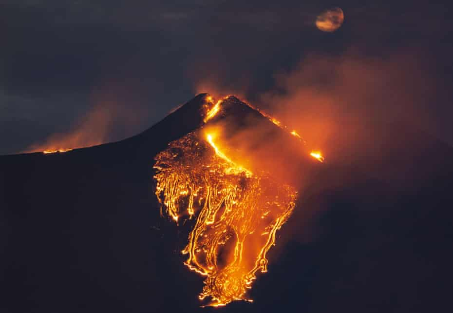 The moon is partially seen in the sky as lava flows from the Mount Etna volcano