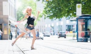 A confident young woman dancing on a city street