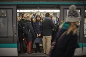 Commuters squeeze into one of the few working metro trains as strikes continue in Paris, France