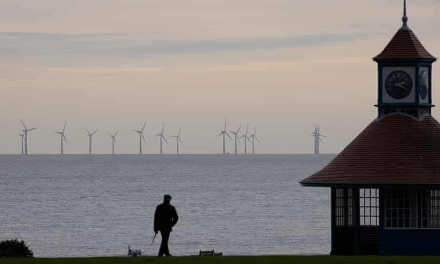 Man walking dog with wind turbines in distance off the coast of Frinton-on-Sea in England.