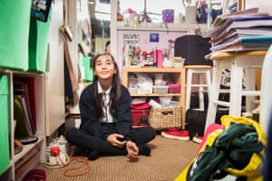 A girl sits on the floor of her bedroom