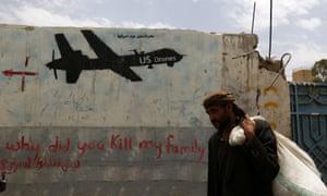 A Yemeni man walks past graffiti showing a US drone after al-Qaeda in Yemen confirmed the death of its leader in US drone strike, in Sana'a, Yemen, 16 June 2015