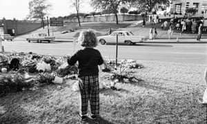 A young girl and a crowd on the Grassy Knoll.