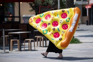 Barcelona, Spain. A woman carries an inflatable float in the shape of a pizza slice