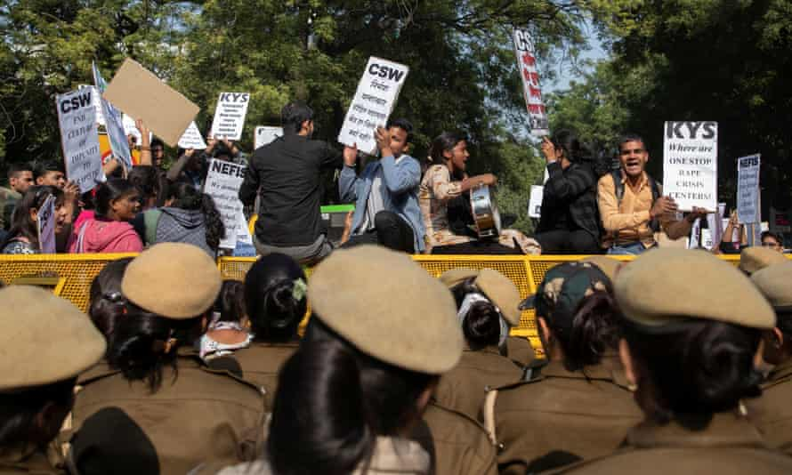 People stand on police barricades as they hold placards and shout slogans during a protest in Dehli