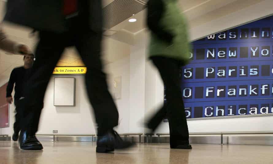 People walking through Heathrow airport.