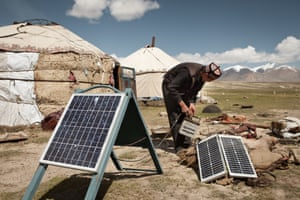 A Kyrgyz man installs solar panels that charge car batteries to provide electricity, mainly for light bulbs and radios, Wakhan, Afghanistan.