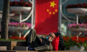A passenger wears a protective mask while resting on the square of Shanghai Railway Station