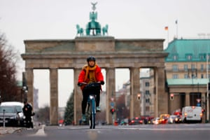 A cyclist is seen on the cycle path along the 17th June boulevard near the landmark Brandenburger Gate in central Berlin.