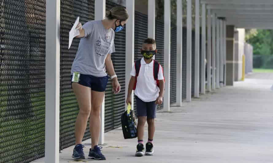 A volunteer escorts a first grader wearing a mask to a classroom on the first day of school in Davie in October 2020.