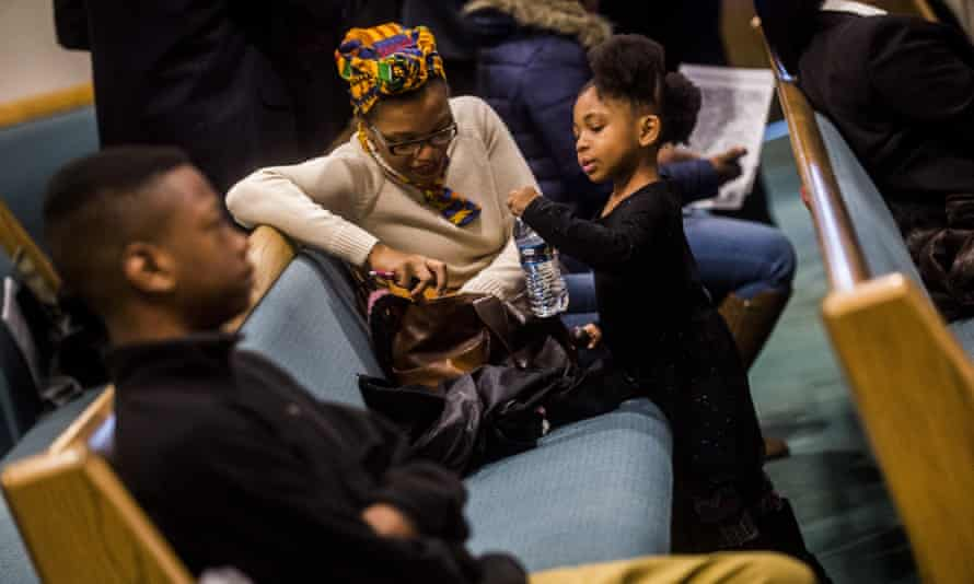 Maya Britton lifts up a bottle of water in the pew alongside her mother Walida Britton, both of Flint, as U.S. Rep. Dan Kildee, D-Flint Township, leads a congressional delegation team of 25 people to listen to Flint residents and understand the water crisis on Friday, March 4, 2016, at Grace Emmanuel Baptist Church in Flint, Mich. (Jake May/The Flint Journal-MLive.com via AP) LOCAL TELEVISION OUT; LOCAL INTERNET OUT; MANDATORY CREDIT