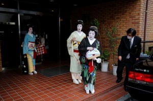 Koiku, Maki and Ikuko, who are geisha, get into a taxi as they make their way to work at a party being hosted by customers at a luxury restaurant