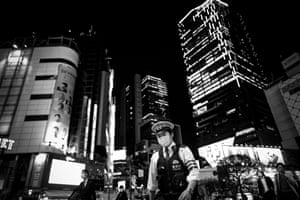A police officer patrols the Shibuya shopping district