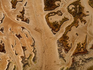 This is an aerial photograph of Sado River Estuary. It shows the intricate patterns shaped by the water flow and salt marshes in a constant and dynamic conflict.