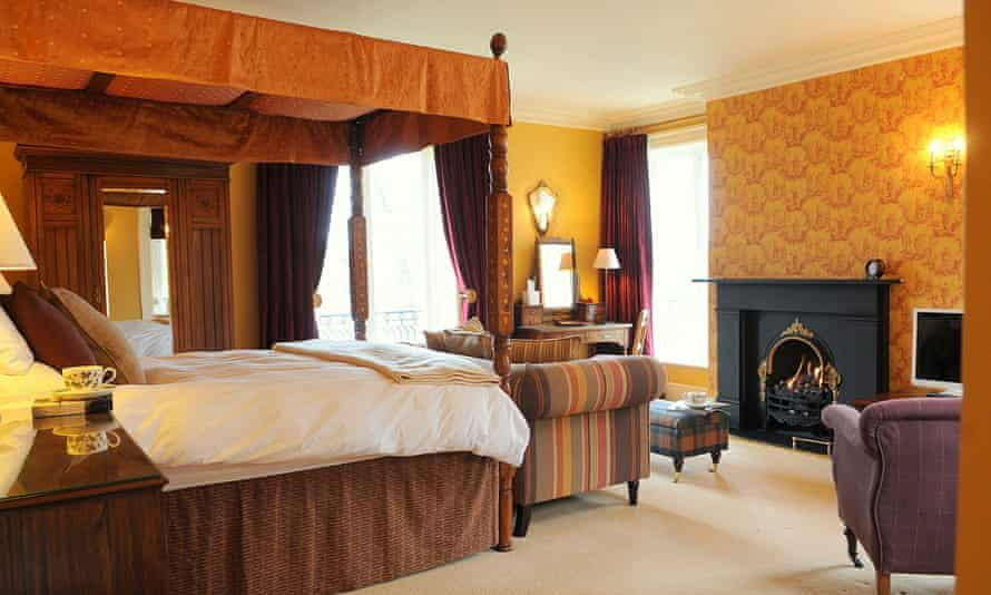 A bedroom with a four-poster and decor in orange hues at Bryniau Golau.