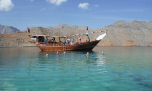 Tourists onboard and around the dhow as part of the Oman fjords swimming holiday