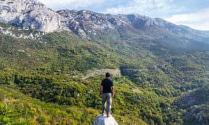 Man stands on a rock looking over the mational park Paklenica, Velebit mountain, Croatia.