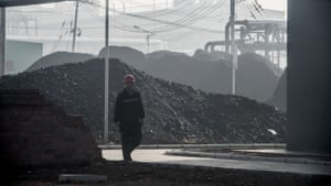 A worker walks by the main gate of a coal-to-oil plant in Changzhi, in Shanxi province, China