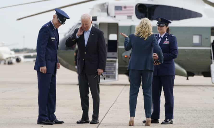 Biden brushes a cicada from his neck as he and the first lady, Jill Biden, prepare to board Air Force One at Joint Base Andrews in Maryland no Wednesday.