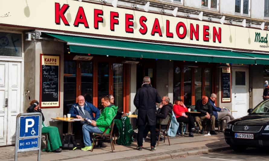 People sit at a cafe in central Copenhagen, Denmark