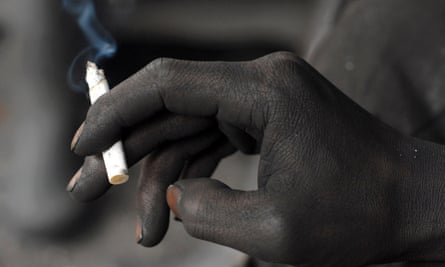 A miner smokes a cigarette during a break at the Gongxigou coal mine on the outskirts of Baokang, Hubei province, December 4, 2007. America taxes cigarettes, but subsidizes fossil fuels.